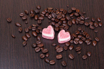 coffee beans and  candies in a heart shape on dark background