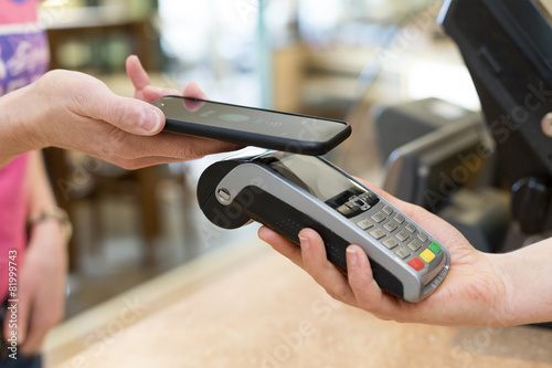 Leinwanddruck Bild customer paying with NFC Technology