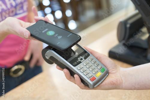 Leinwandbild Motiv customer paying with NFC Technology