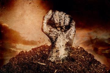 Dreckige Faust steigt aus Erde