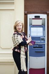 Mature blonde woman with credit card in hand near ATM