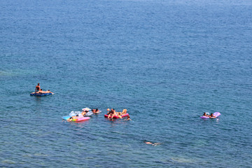 spiaggia siciliana con ragazzi a mare