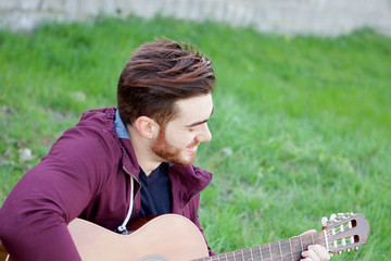 Cool handsome guy with beard playing guitar