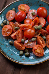 Sliced tomatoes with capers, sea salt and pepper, close-up
