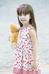 Happy little girl smiling outdoors with teddy bear