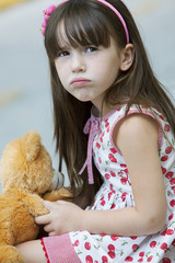 Little girl with teddy bear, sulking