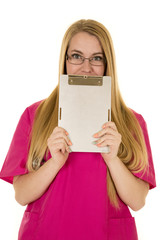 nurse pink clothes and glasses with clipboard in front of face
