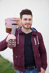 Handsome man carrying a guitar on his shoulders