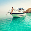 Leinwandbild Motiv Beautiful young woman on boat. Luxury vacation at sea on yacht.
