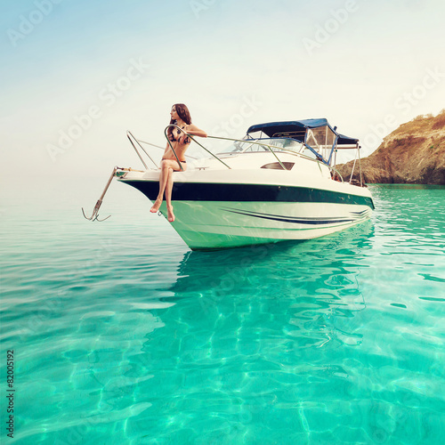 Leinwanddruck Bild Beautiful young woman on boat. Luxury vacation at sea on yacht.
