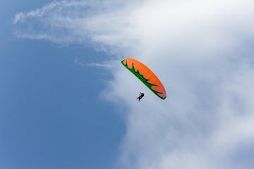 Orange-green tandem paragliders on the blue sky