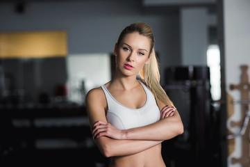 Beautiful athletic girl  poses in the gym
