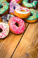 Colorful glazed donuts on the wooden table