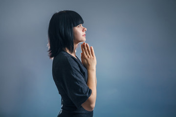 European appearance brunette girl clasped her hands in prayer on