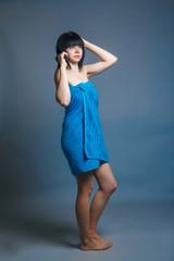 European appearance brunette girl wrapped in a blue towel combin