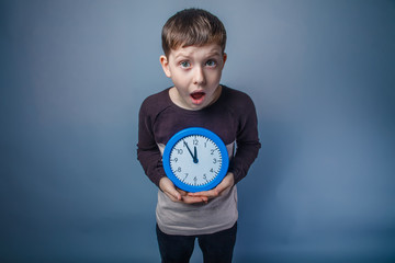 boy teenager European appearance holds a clock blue and opened h