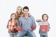 Happy family of four isolated holding gifts