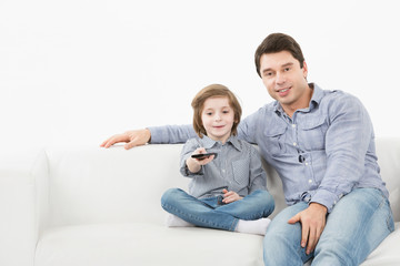 Father and son sitting on the couch with the TV remote control.