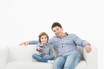 Family watching television sitting on sofa at home
