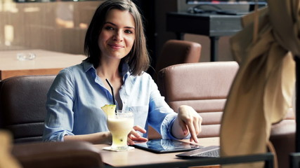 Portrait of happy woman with tablet computer and cocktail