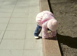 little girl climbing over the border