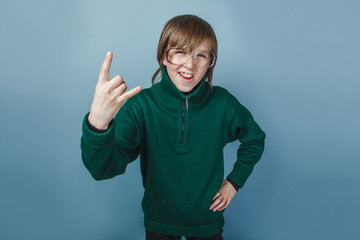 European-looking boy of ten years showing thumbs up on a gray  b