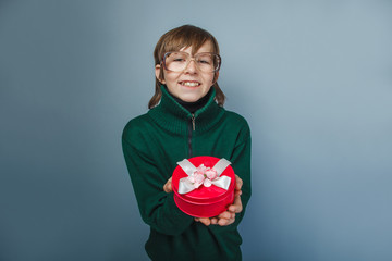 European-looking boy of ten years in glasses holding a gift box