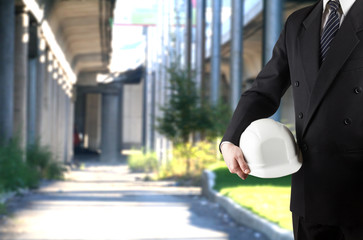 Close up of engineer hand holding white safety helmet for worker