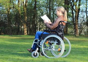 Frau im Rollstuhl liest Buch im Park.JPG