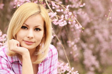 Girl with Cherry Blossom. Beautiful Blonde Young Woman