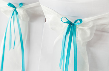 Wedding chairs with blue ribbons.