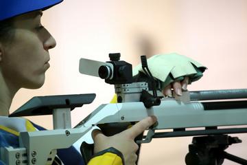 woman aiming a pneumatic air rifle