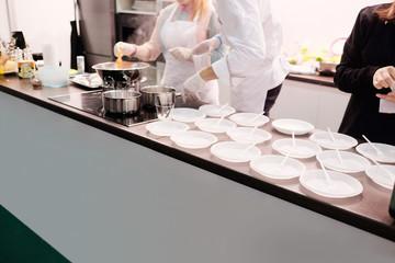 Chefs preparing food, empty plastic plates on the rack