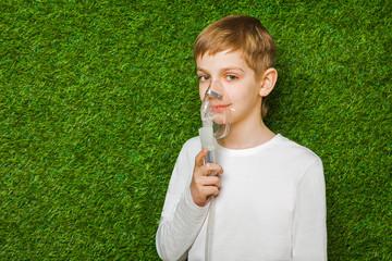 portrait of a boy breathing through inhalator mask