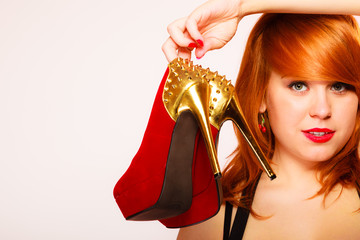 Attractive woman holding high heel shoes.