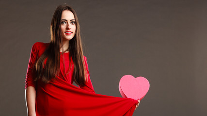 Woman red dress holds heart shaped box