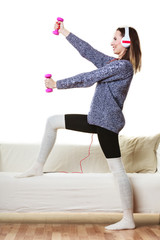 woman exercising with dumbbells listening music