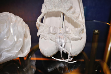 White Brides shoes and garter on table