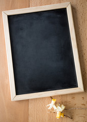 Closeup of small blackboard lying on table with dried flowers
