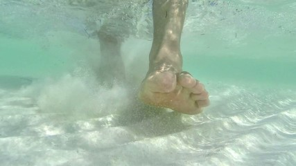 Closeup underwater barefeet walking over shallow sandy sea floor
