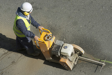 worker using cutting  pavement machine in the city road