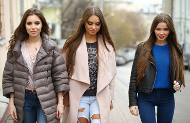 Three young beautiful girlfriends in autumn clothes walking on t