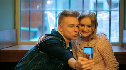 Couple doing selfie in the cafe on smartphone