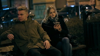 Woman texting on smartphone and uhappy boyfriend looking at her