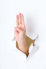 Woman breaking through a paper wall showing three finger