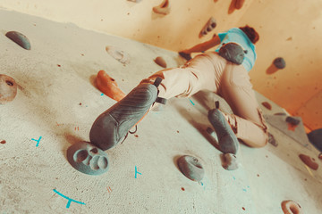 Woman climbing artificial boulder