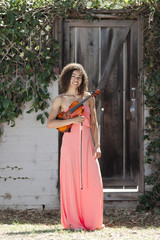 Young woman in pink dress holding violin outside