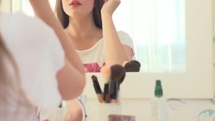 Beautiful girl looking in the mirror and applying mascara