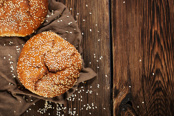 Fresh rye buns with sesame seeds on a wooden background
