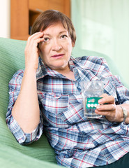 sad female pensioner with pills and glass of water